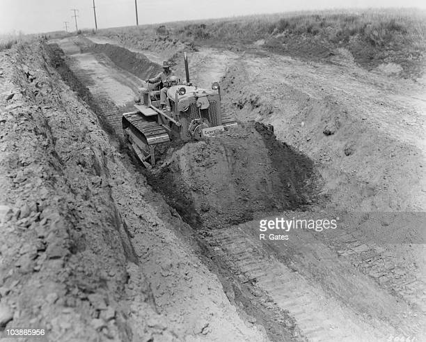 A 'Caterpillar' Diesel D7 Tractor with a No 7S Bulldozer and No 24 Cable Control cutting through a hill during highway preparations near Pasco...