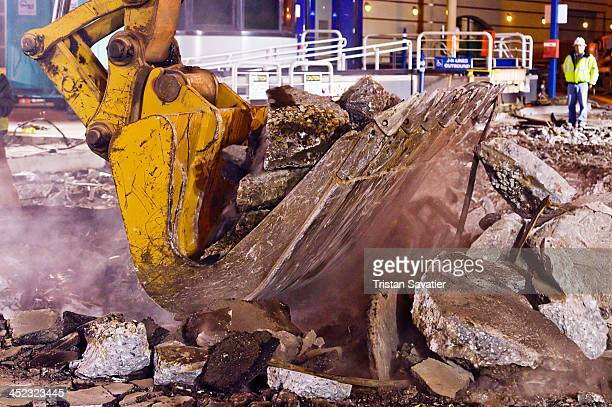 CONTENT] Caterpillar excavator shoveling concrete debris Railroad workers were replacing a Muni light rail track section at Duboce street and Church...