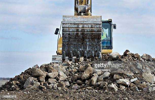 A Caterpillar Inc 330DL track excavator loads rocks into a Knife River Corp dump truck in a farmer's field for road construction and drainage outside...