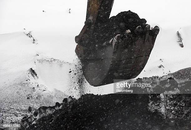 A Caterpillar Inc 375 Hydraulic Excavator digs coal from a snow covered heap at the Raspadsky open pit mine operated by Evraz Plc in Mezhdurechensk...