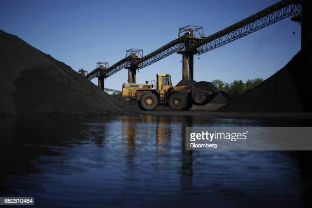 A Caterpillar Inc 988F wheel loader works beneath coaling towers at the SunCoke Energy Partners LP Ceredo Terminal in Ceredo West Virginia US on...