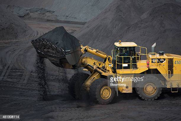 A Caterpillar Inc bulldozer collects a shovel of coking coal before loading it into a waiting truck in a storage dump at the Elga coal complex...