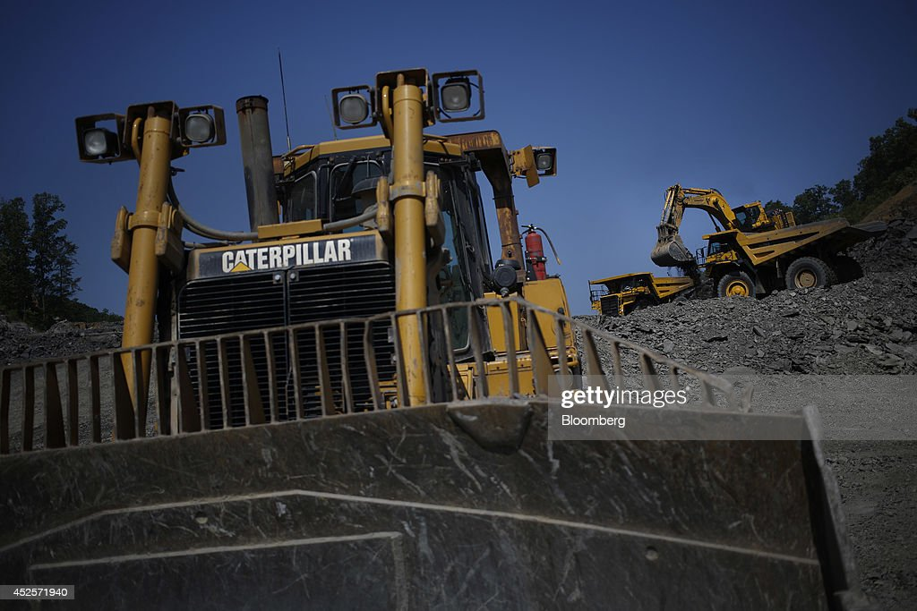 A Caterpillar Inc. bulldozer sits nearby as an excavator distributes loads of blasted rock into dump trucks during the construction of a new segment of U.S. Highway 460, part of the Appalachian Development Highway System, under construction near the Virginia border in Elkhorn City, Kentucky, U.S. on Tuesday, July 22, 2014. Senate Democrats may bring to the floor a House-passed measure that would replenish federal funds for highway and mass-transit projects through May 2015. As part of that debate, senators could vote on two Democratic alternatives, although leaders say the House measure is more likely to prevail. Photographer: Luke Sharrett/Bloomberg via Getty Images
