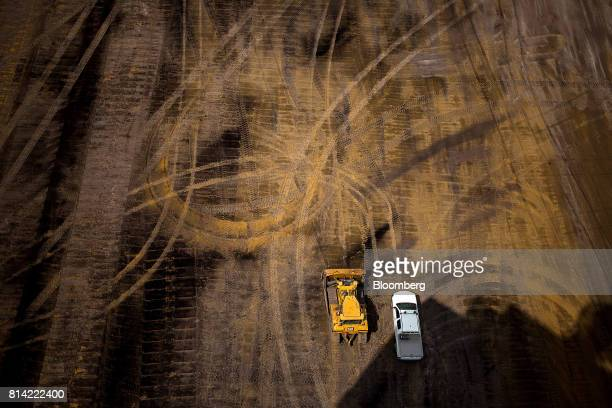 A Caterpillar Inc earthmover stands beside a truck at the Garzweiler open cast lignite mine operated by RWE AG in Garzweiler Germany on Thursday July...