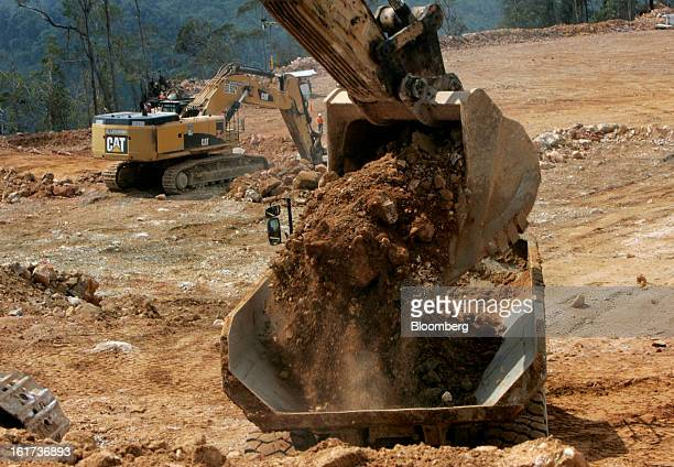 A Caterpillar Inc excavator loads ore onto a dump truck at the GResources Group Ltd Martabe gold and silver mine in Batang Toru North Sumatra...