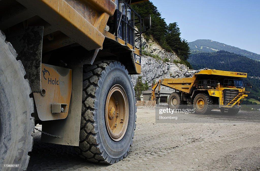 Caterpillar Inc , left, and Komatsu Ltd  dumper trucks stand