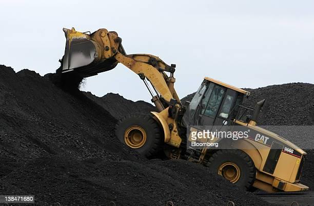 A Caterpillar Inc machine operates at a coal stockpile site at the Onahama port in Iwaki City Fukushima Prefecture on Monday Feb 6 2012 Japan's...