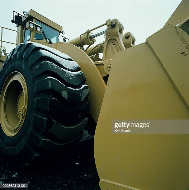 Caterpillar model tractor on road construction site, low angle view