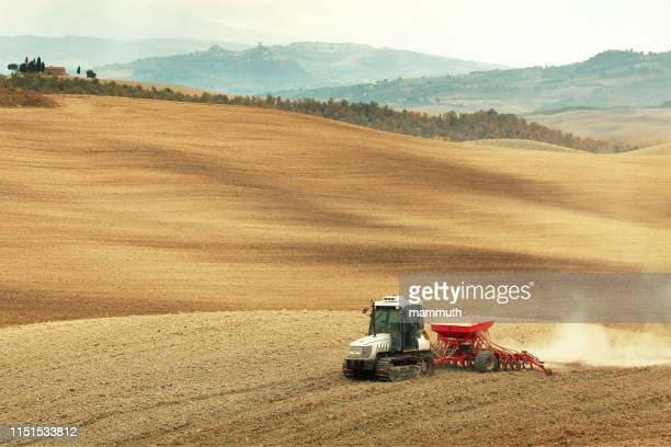 caterpillar tractor pulling seeder and harrow - tiller stock photos and pictures