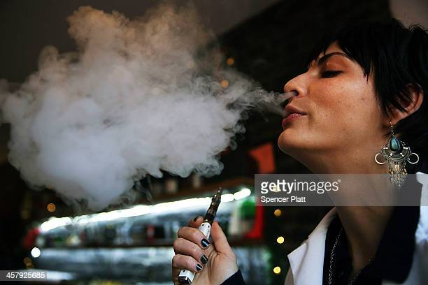 Catharine Candelario an employee at the newly opened Henley Vaporium vapes or smokes an electronic cigarette on December 19 2013 in New York City The...