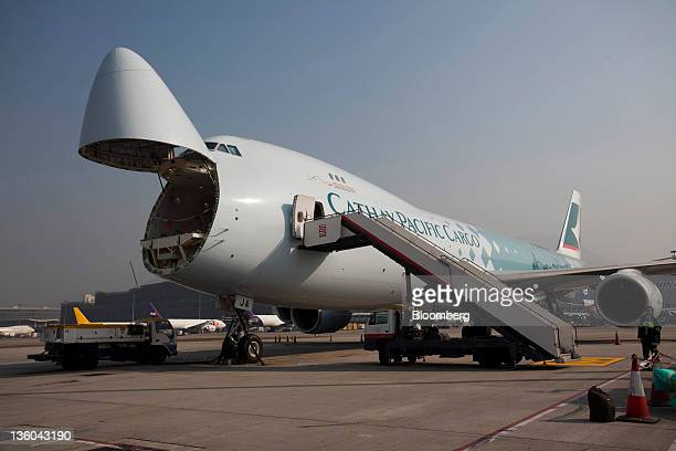 A Cathay Pacific Airways Ltd Boeing Co 7478 freighter with an open nose door sits on the tarmac at Chek Lap Kok Airport in Hong Kong China on Monday...