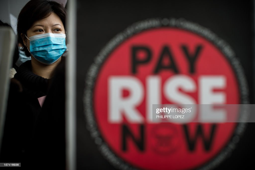 A Cathay Pacific flight attendant stands next a placard as she and others stage a protest at the international airport in Hong Kong on December 3, 2012. The employees of the Hong Kong flag carrier staged the protest to voice their discontent at the company's decision of an average 2 per cent pay rise for Hong Kong ground staff and cabin crew, claiming it was less than the average 5 per cent rise and below current inflation levels. AFP PHOTO / Philippe Lopez