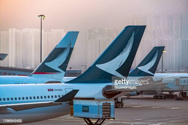 cathay tails with high rise in hazy background - airplane tail stock pictures, royalty-free photos & images
