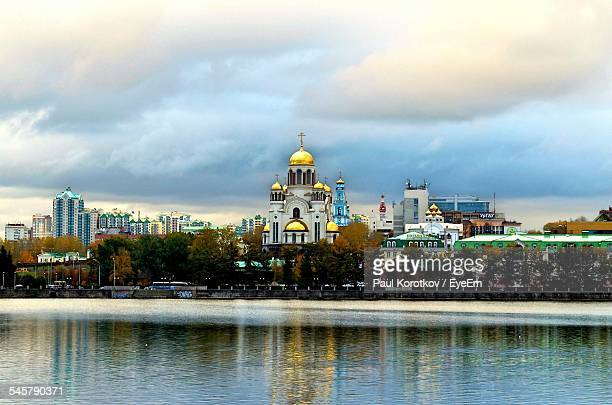 Cathedral In City By River Against Cloudy Sky