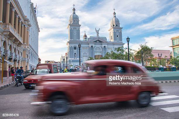 Cathedral Our Lady of Asuncion in the Cespedes plaza. Old American car as taxi and moving in the tropical city. The church and old cars are a major...