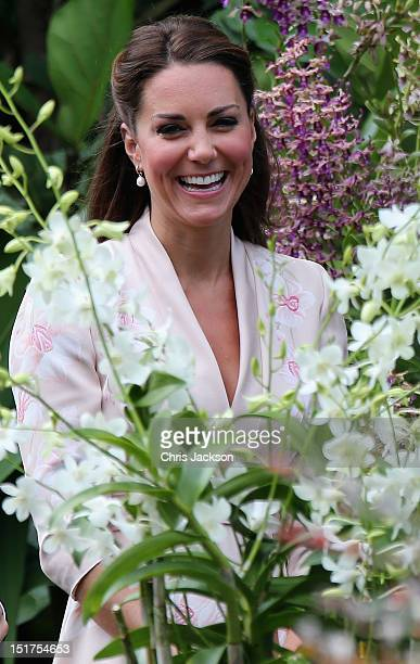Catheine Duchess of Cambridge smiles as she looks at an orchid named in honour of Diana Princess of Wales at Singapore Botanical Gardens ahead of a...
