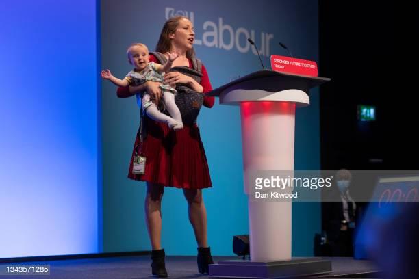 Catherine Atkinson, whose husband served in Afghanistan, holds nine month old Elena as she addresses delegates on September 28, 2021 in Brighton,...