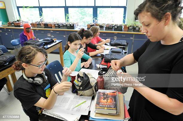 Catherine Bursk helps her students Natasha Malia left and Lilly Russell right read the test strips as her seventh grade class at King Middle School...