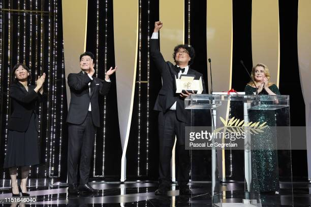 Catherine Deneuve applauds as Lee JungEun KangHo Song and Bong JoonHo celebrate after receiving the Palme d'Or award for the film Parasite at the...