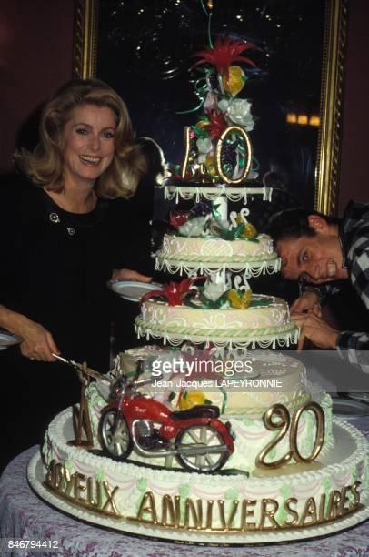 Catherine Deneuve decoupe un enorme gateau d'anniversaire lors de la fete de ses 40 ans avec son fils Christian le 27 octobre 1983 a Paris, France.
