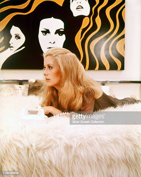 Catherine Deneuve French actress laying on a fur surface with an artwork hanging on the wall behind her in a publicity still issue for the film...