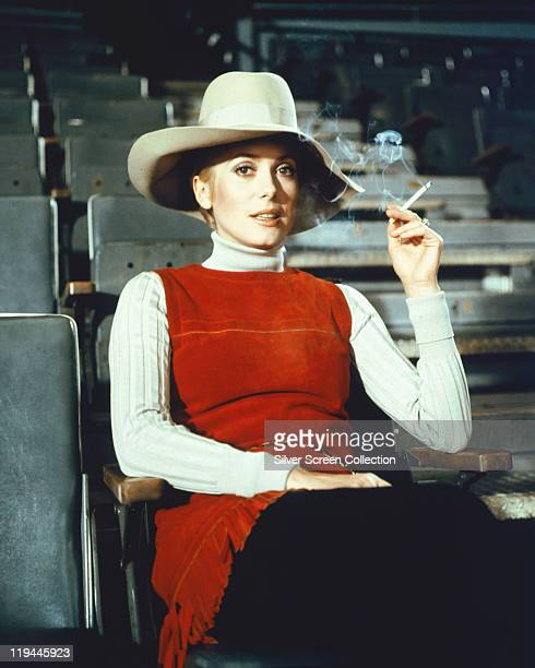 Catherine Deneuve French actress smoking a cigarette while wearing a widebrimmed hat a red sleeveless top and a white polo neck jumper in a publicity...