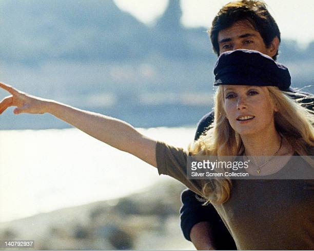 Catherine Deneuve, French actress, wearing a dark blue peaked cap and holding her right arm out as if hitchhiking, circa 1970.