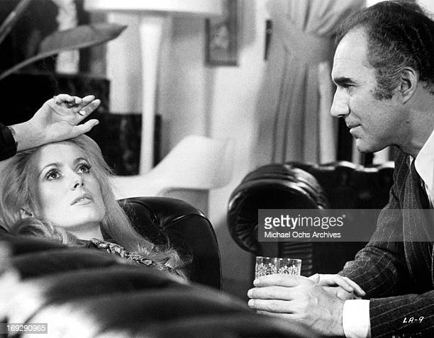 Catherine Deneuve laying down next to a sitting Michel Piccoli in scene from the film 'Heartbeat', 1968.