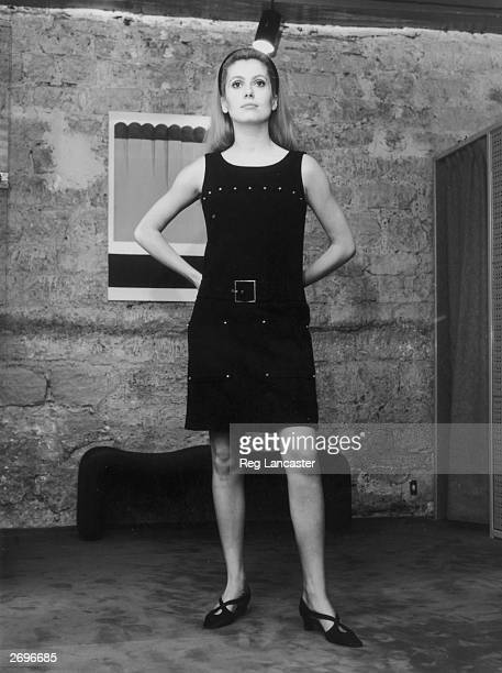 Catherine Deneuve modelling a 'small black dress' from ' Rive Gauche', Yves Saint Laurent's ready-to-wear boutique collection. The dress has no...