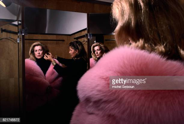 catherine deneuve trying on pink fur coat - pink coat stock pictures, royalty-free photos & images