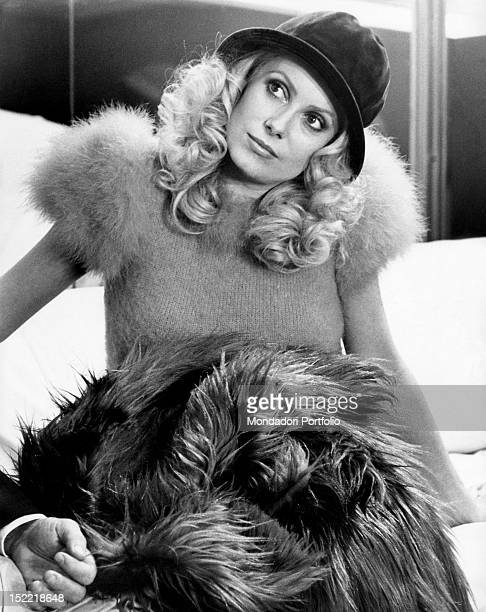 Catherine Deneuve with her head slightly turned and a fur coat in her lap Paris 1973