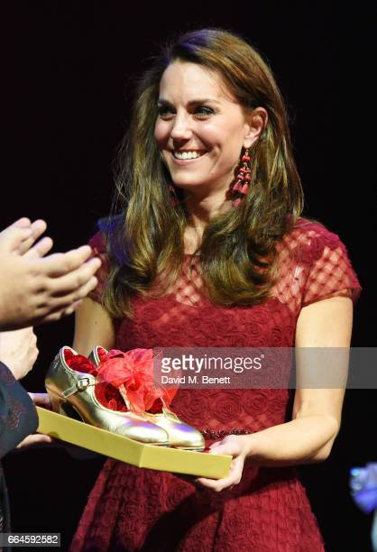 Catherine Duchess of Cambridge accepts a gift of tap shoes during the Opening Night Royal Gala performance of 42nd Street in aid of the East Anglia...