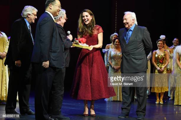 Catherine Duchess of Cambridge accepts a gift of tap shoes from producers Michael Linnet Michael Grade and director Mark Bramble during the Opening...