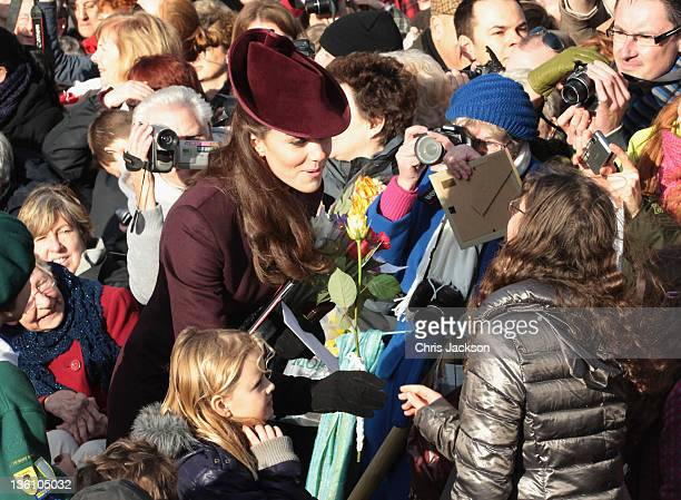 Catherine, Duchess of Cambridge accepts flowers from members of the crowd as she leaves Sandringham Church after the traditional Christmas Day...
