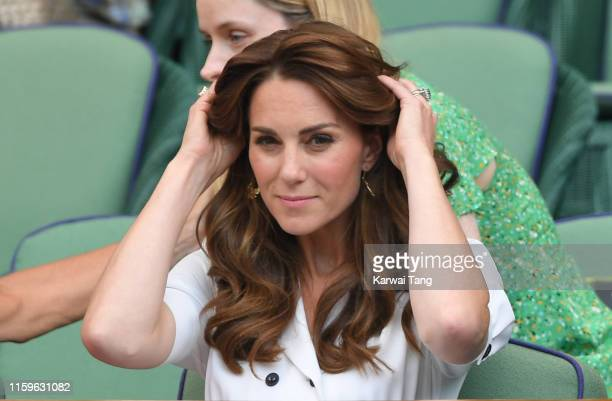 Catherine Duchess of Cambridge adjusts her hair as she attends day 2 of the Wimbledon Tennis Championships at the All England Lawn Tennis and Croquet...
