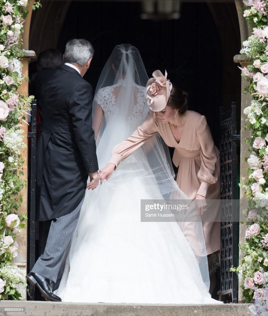 Catherine, Duchess of Cambridge adjusts Pippa's wedding dress as they arrive for the wedding Of Pippa Middleton and James Matthews as a page boy gestures at St Mark's Church on May 20, 2017 in Englefield Green, England.