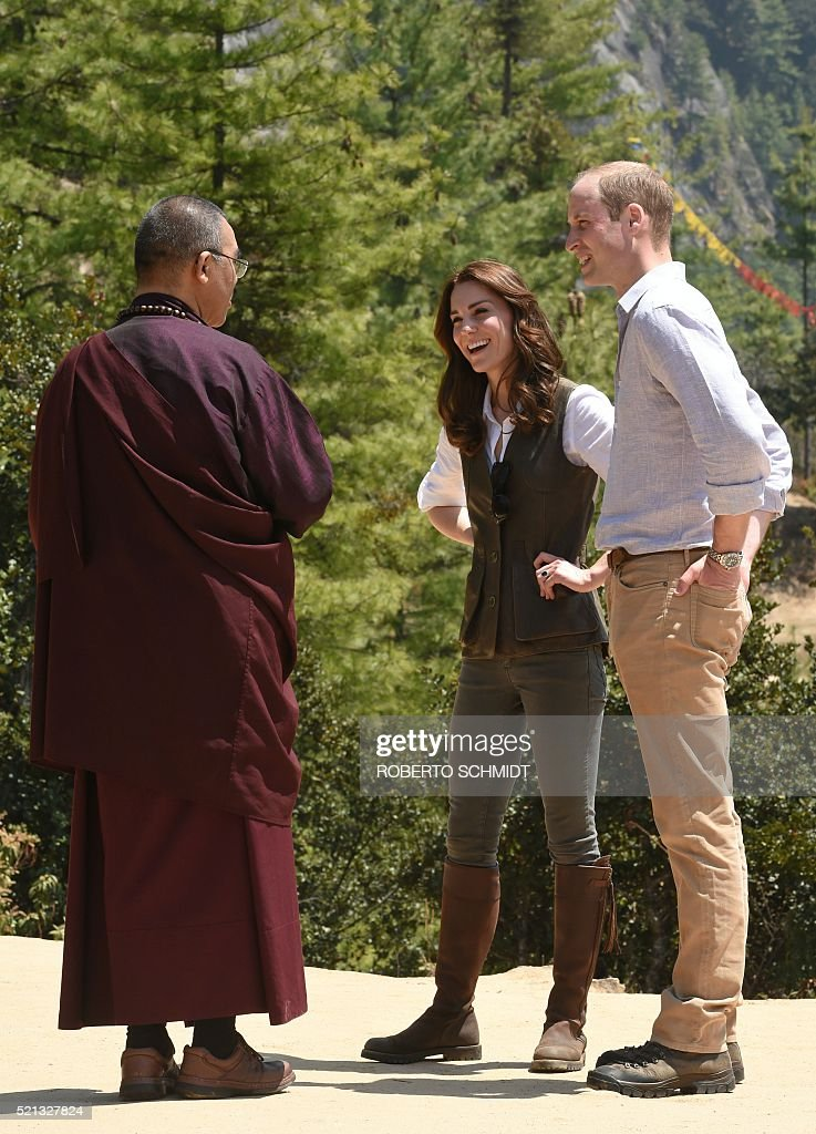 Catherine Duchess of Cambridge(C) and Britain's Prince William Duke of Cambridge(R)speak with a Buddhist monk as they halt while walking the trail up to a Buddhist monastery referred to as 'Tiger's Nest' to Paro Taktsang on the outskirts of Thimphu on April 15, 2016, during their two day visit to Bhutan. / AFP / ROBERTO