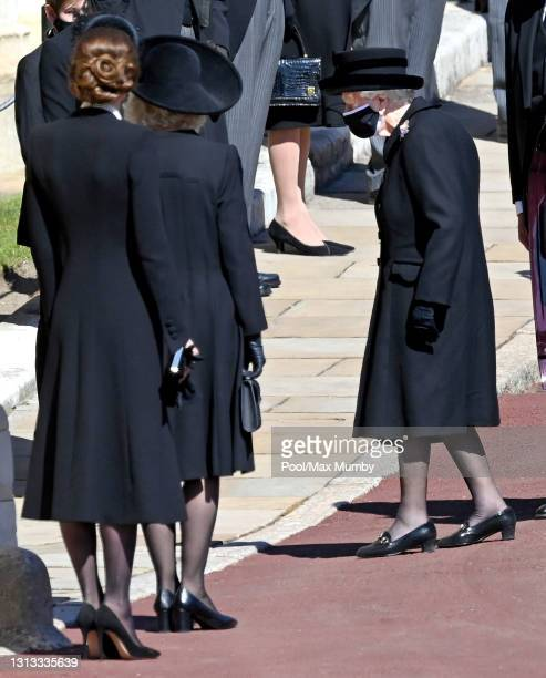 Catherine, Duchess of Cambridge and Camilla, Duchess of Cambridge look on as Queen Elizabeth II arrives attend the funeral of Prince Philip, Duke of...