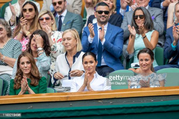 Catherine Duchess of Cambridge and Meghan Duchess of Sussex and Pippa Middleton in the Royal Box applaud the players as they arrive on Centre Court...