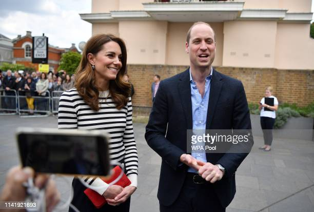 Catherine Duchess of Cambridge and Prince William Duke of Cambridge talk to members of the media about their newborn nephew as they arrive to launch...