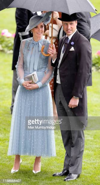 Catherine, Duchess of Cambridge and Prince William, Duke of Cambridge shelter under an umbrella as they attend day one of Royal Ascot at Ascot...