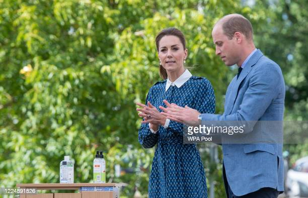 Catherine, Duchess of Cambridge and Prince William, Duke of Cambridge apply hand sanitizer during their visit to Queen Elizabeth Hospital in King's...