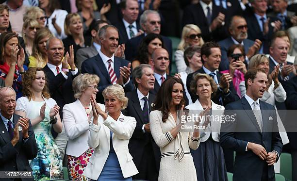 Catherine Duchess of Cambridge and Prince William Duke of Cambridge applaud from their seats in the Royal Box on Centre Court during day nine of the...