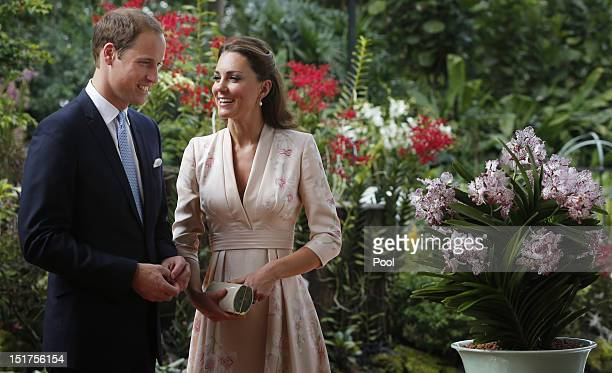 Catherine, Duchess of Cambridge and Prince William, Duke of Cambridge smile as they look at an orchid named in honour of Diana, Princess of Wales at...