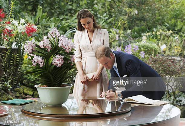 Catherine Duchess of Cambridge and Prince William Duke of Cambridge sign the visitors book during a visit Singapore Botanical Gardens on day 1 of...