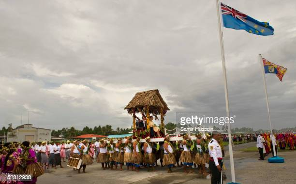 Catherine Duchess of Cambridge and Prince William Duke of Cambridge are carried to a welcoming ceremony when they arrive at Funafuti airport during...