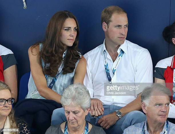 Catherine Duchess of Cambridge and Prince William Duke of Cambridge hold hands as they watch the swimming at Tollcross Swimming Centre during the...