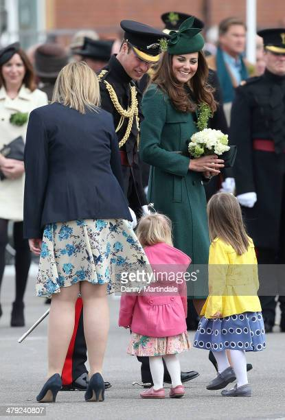 Catherine Duchess of Cambridge and Prince William Duke of Cambridge talk to two children during the St Patrick's Day parade at Mons Barracks on March...