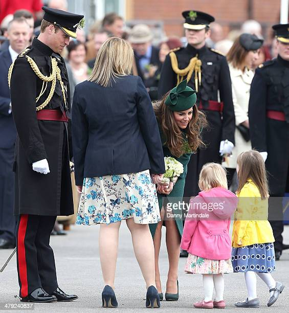 Catherine, Duchess of Cambridge and Prince William, Duke of Cambridge talk to two children during the St Patrick's Day parade at Mons Barracks on...