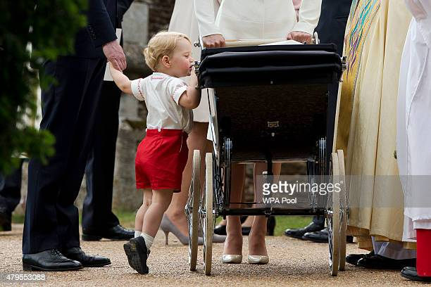 Catherine, Duchess of Cambridge and Prince William, Duke of Cambridge stand as Prince George of Cambridge looks into Princess Charlotte of...